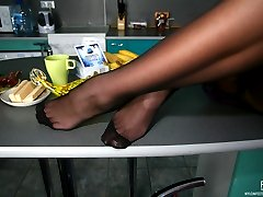 Leggy vixen dangles her shoe and flashes nyloned feet dancing on the table