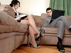 Businessman putting aside laptop looking at pantyhosed babe dangling shoes