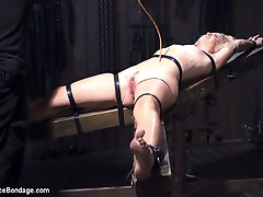 Dylan is restrained in wooden stocks around her neck and wrists. Her ankles are locked down in...