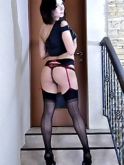 Dark-haired sexpot in black stockings and spike heels flashes on the stairs