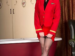 Brook is one sexy air hostess in her clingy red uniform with sheer black nylon blouse and red patent stilettos!