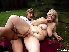 She is bent over and on the grass and she is taking cock in her sexy mature pussy