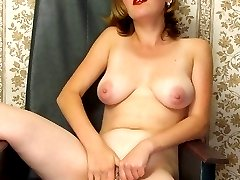 Pretty mature blonde strips off her clothes to play with her tits and rub her bushy cunt