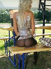 Long-haired blondie giving a glimpse of her slender legs in black pantyhose