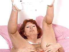 Sexy redhead grandma playfully stripping off her clothes to cram a dildo in her ass