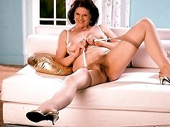 Naughty granny Joanna serves up her steaming pussy with a smile as she strips down in the living room