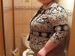 Mature woman with a hairy by a pussy, pissing in the toilet)
