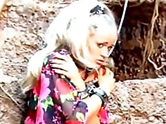 Mistress in stockings and latex cat lady mask suspends and fucks her blonde slave outdoors