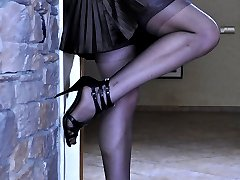 Dressed like a goth chick licks her black stockings and flashes her bush