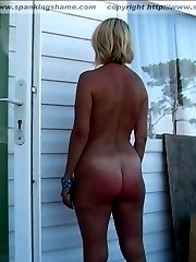 Naked mature woman is spanked until her buttocks are burned red