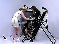 Two hot dominas in latex gagging a pretty lesbian slave before training her