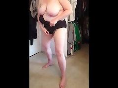 squeezing her bbw body, big tits into black girdle
