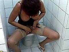 Redhead mature masturbates in a restroom