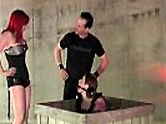 Dominant couple submitting brunette sub in private dungeon