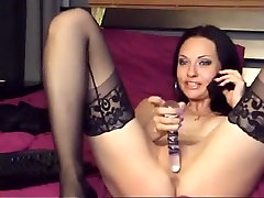 Sultry chick in black stockings masturbates while talking on the phone