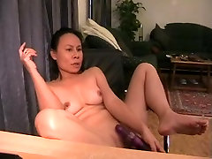 Mature Oriental wife masturbates her twat with a sex toy