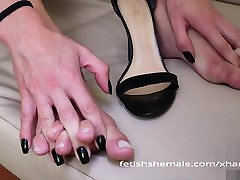 Ms Cristina rubbing her sexy shemale feet after hard day