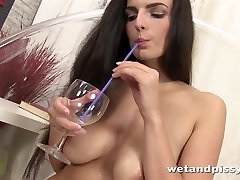 Gorgeous brunette sips her own golden piss through a straw